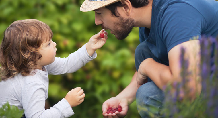 daughter feeding dad fruit
